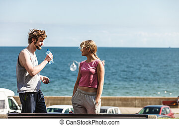 Woman and man drinking water outdoor Young couple taking...