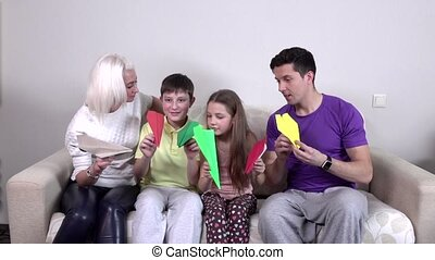 Family launches colorful paper airplanes in the room,...