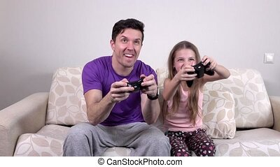 Father and daughter playing a video game, slowmotion -...