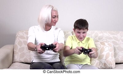 Little boy with mom playing video games at home, slowmotion...