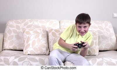 Little boy playing video games at home, slowmotion