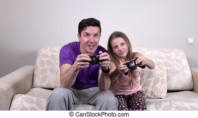 Father and daughter with video game controllers, slowmotion...