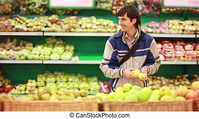 Man has a fun while takes an apple in a grocery store....