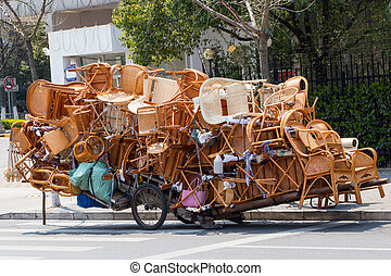 Overloaded chinese transport cart with far too many chairs
