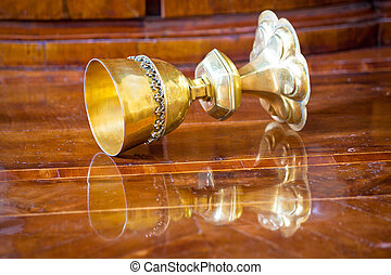 Golden grail turned on wooden background surface