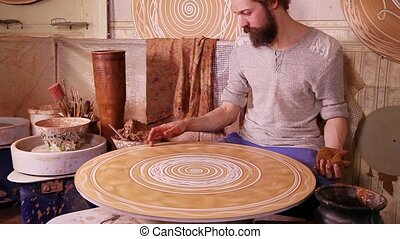 Craftsman creating a decorative pan - Craftsman creating a...