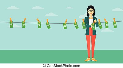 Woman loundering money - An asian business woman drying...