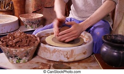 Potter works in his workshop - Potter putting clay on the...