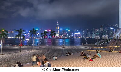 Hong Kong city skyline at night over Victoria Harbor with clear sky and urban skyscrapers timelapse hyperlapse.