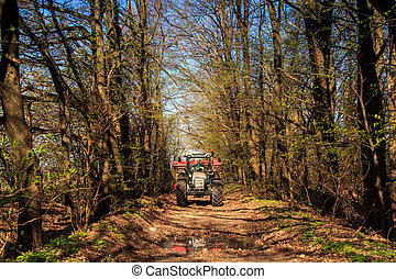 tractor on soil road in spring forest against blue sky