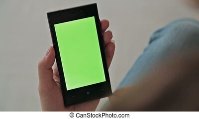 Woman using a mobile phone with green screen, scrolling...
