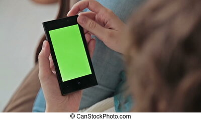 Woman using a mobile phone with green screen and scrolling