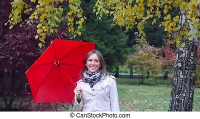 Beautiful happy girl with red umbrella at autumn park during...