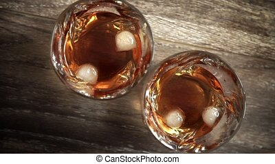 Glasses of whiskey with ice on wooden table.