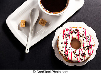 Top view of donut and cup coffee on black background