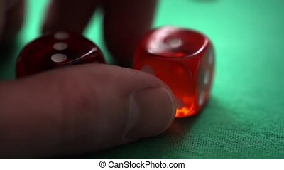 Red dice in hand on green table