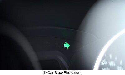 Turn signal light blinking on black car Inside shot