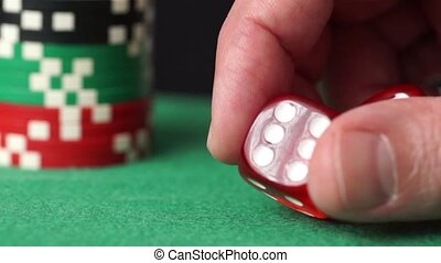 Red dice and casino chips in hand on green table