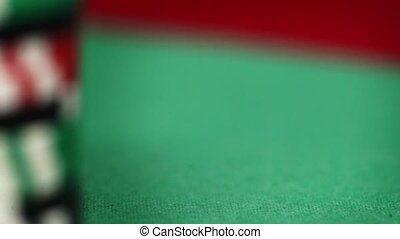 Red dice rotation and casino chips on green felt - The red...