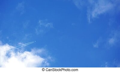 Airplane disappearing vapor trails against a cloudy blue sky