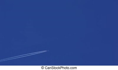 Airplane disappearing vapor trails against a clear blue sky