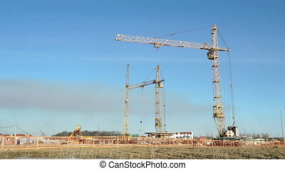 Construction cranes operate on the object - Beginning of...