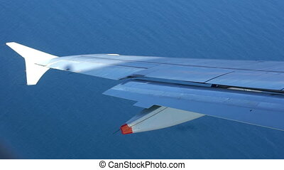 Aircraft wing above water surface - Aircraft wing above blue...