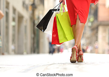 Shopper woman legs walking with shopping bags - Back view of...