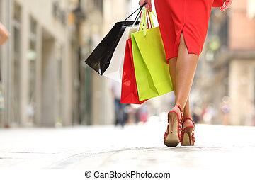 Shopper woman legs walking with shopping bags