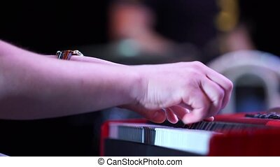Professional hand playing on keyboard synthesizer -...