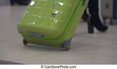 Woman with suitcase in hall of airport - Woman with green...