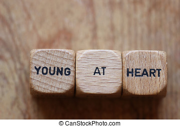 Young at heart printed on three wooden dice with room for...