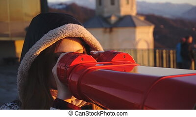 Tourist looking at city through coin-operated binoculars at sunset, tight shot