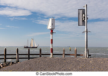 Old wooden sailing ship seen from port pier of Urk, The Netherlands
