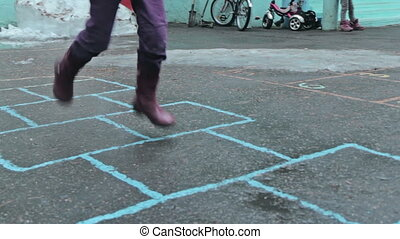 Kids playing hopscotch near kindergarden