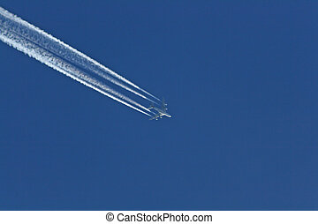 Jet with vapor trail at deep blue sky