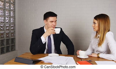 Two happy businesspeople with coffee at office talking - Two...