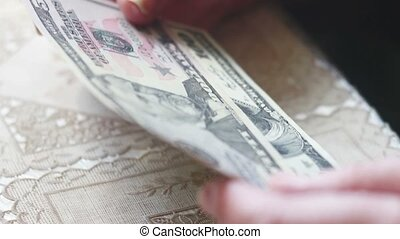 Closeup of senior lady hands with dollar bills, toned color,...
