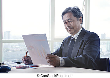 senior working man reading business paper report on working...