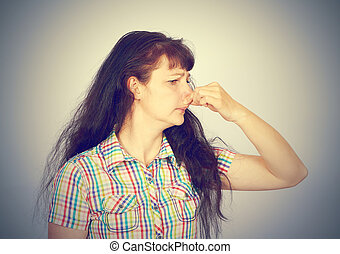 young woman holding her nose because of bad smell on a gray...