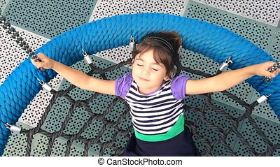 Girl play on a net swing - Slow motion of a girl on a net...