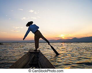 Silhouette fishermen in Inle Lake at sunrise, Shan State,...