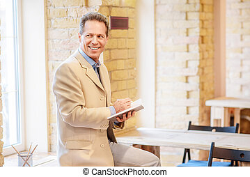 Cheerful man making notes - Keep it in your mind. Positive...