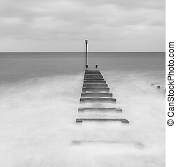 Black and white long exposure landscape image of sea and...