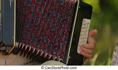 Man Playing The Accordion Outdoors - CLOSE UP. Hands of male...