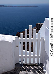 Small white fence gate and sea view on Santorini island,...