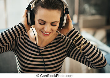 Woman listening to music in loft apartment Close up portrait...