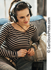 Woman listening to music through headphones in loft...
