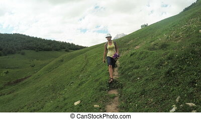 Path in alpine meadows woman - Camera on steadicam moves...
