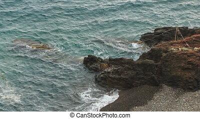 Foamy Waves of Blue Sea Strike Stones of Beach - foamy waves...